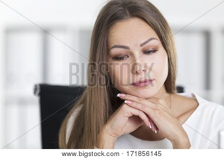 Close up of a sad blond woman in a white office. She is sitting with her chin on her hands and looking into distance.