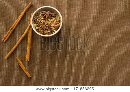 Overhead view of a bowl of mulling spices and cinnamon sticks.