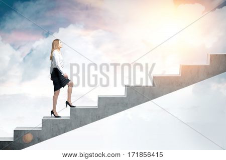 Side view of a blond woman in a black skirt and a white blouse and climbing stairs to the sky. Concept of a road to success in business.