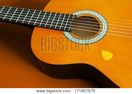 Closeup detail of a classic guitar and yellow plectrum over orange background