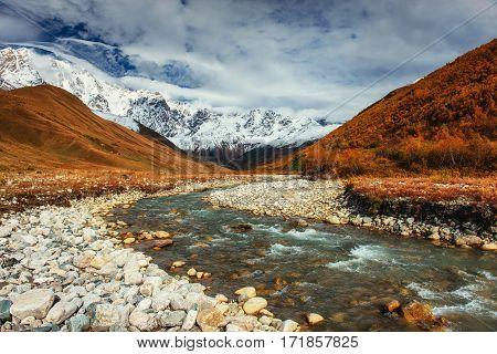 Snowy mountains and noisy mountain river. Georgia Svaneti. Europe
