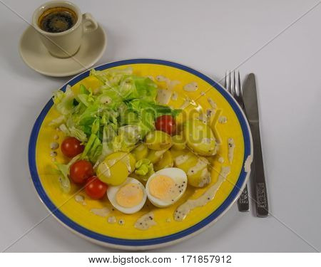 salad with potatoes cherry tomatoes and eggs chipped on a yellow plate black coffee in a cup vegetarian dish