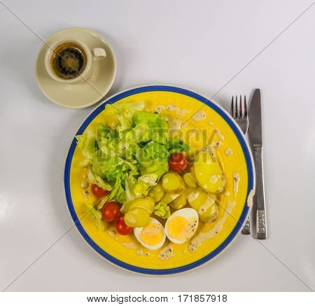 top view on salad with potatoes cherry tomatoes and eggs chipped on a yellow plate black coffee in a cup vegetarian dish
