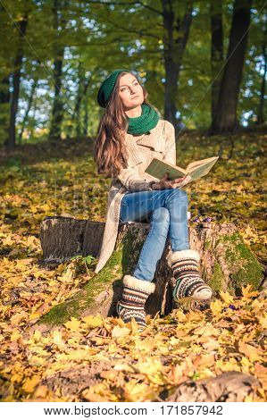 girl sitting on a stump and reads a book in the park