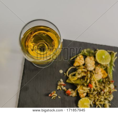 White wine in a glass of wine in the background thai chicken with basmati rice oriental dish