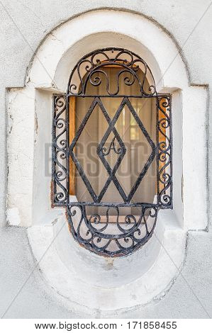 Old window on Murano island, Venice Italy with ornamented metal letter A.
