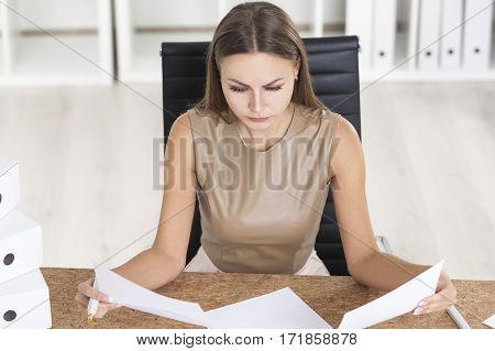 Portrait of a woman in beige at her cork table looking at two documents and looking for a deference.