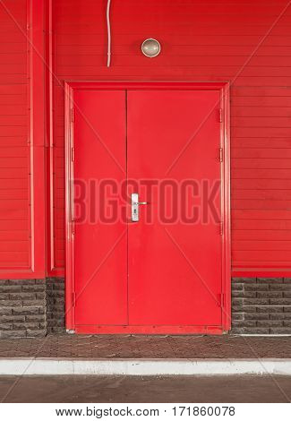 Red door in red wall with a lamp