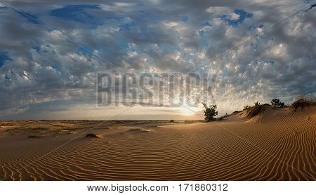 Sunset with spectacular clouds over sandy desert