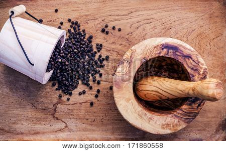 Closeup Black Pepper In Wooden Pot And Mortar On Shabby Teak Wood Table. Seasoning And Species Ingre