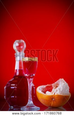 sweet grapefruit alcoholic cordial in the decanter with a glass on a red background