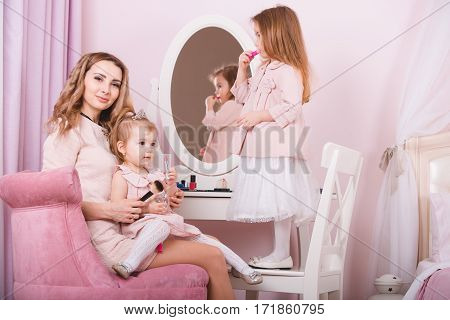 Mother and two daughters doing lip make-up near dress table.