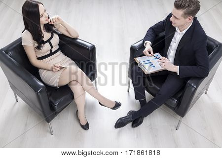Man With Clipboard And Woman In Armchair