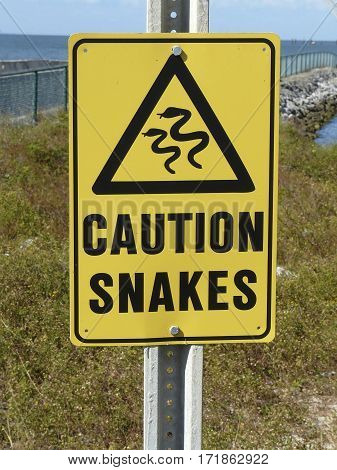 Caution sign warning visitors of snakes in the area at a public ferry landing for transportation across Mobile Bay, Alabama.