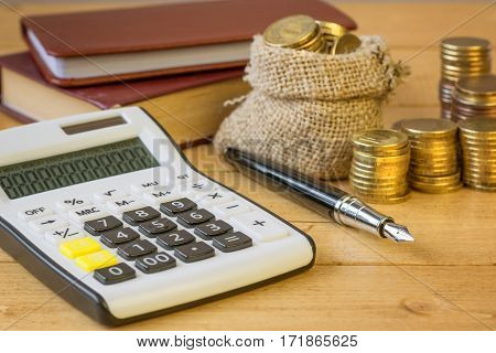 Metal Coins And Calculator On A Rustic Table.