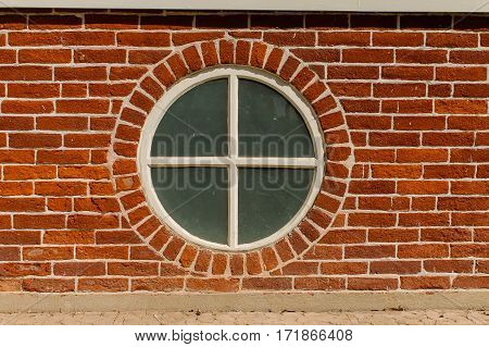 Quartered round wood framed window encased in Red Briack