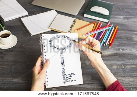 Close up of girl's hands drawing business keys in spiral notepad above wooden desktop with coffee cup and supplies