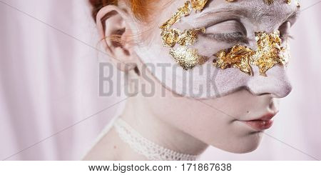 The girl in a mask of sumalnogo gold with white makeup and white eyelashes on a white background. Pale skin eyes closed. The ribbon on the neck.