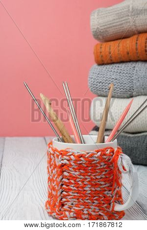 Knitted wool sweaters. Pile of knitted winter autumn clothes on wooden background sweaters knitwear cup pen leaf space for text
