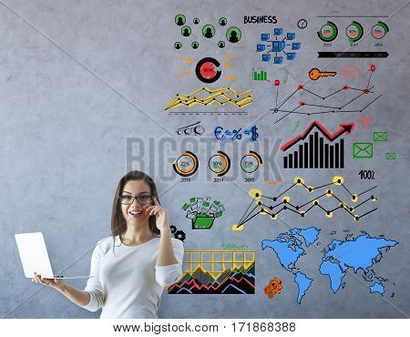 Happy young businesswoman with open laptop talking on the phone in concrete room with colorful charts. Business communications concept