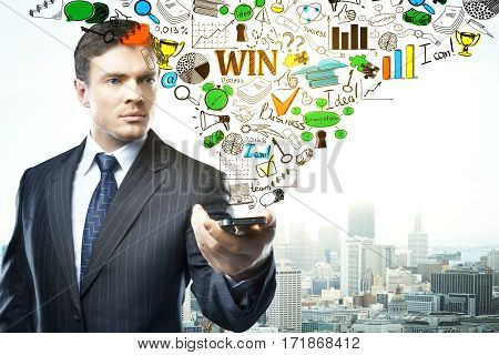 Focused businessman holding smartphone with abstract business sketch on city background. Technology concept