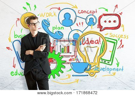 Thoughtful young businessman with smartphone on brick background with colorful business sketch. Communication concept
