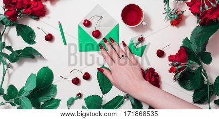 Woman's hand with red nails with a silver ring with black stone corundum and rim theon. Red tea small envelopes with green leaves roses lay on white background. Healing drink. Send mail flat lay.