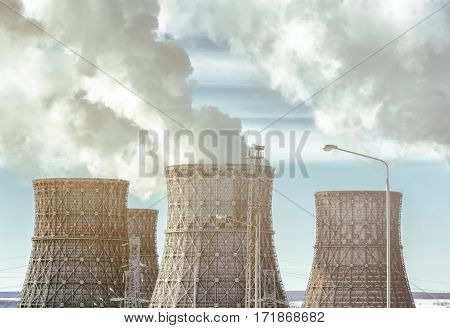 Cooling towers of nuclear power plant with steam or smoke from heat energy. Toned photo