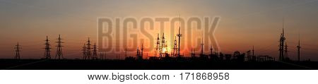 Silhouettes of electric poles and wires at sunset