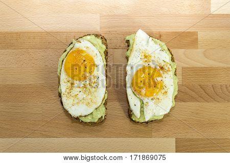 Healthy avocado toast and fried egg on whole grain bread on wooden background for breakfast