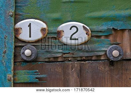 Enameled metal plates with the numbers of apartments on the old wooden door