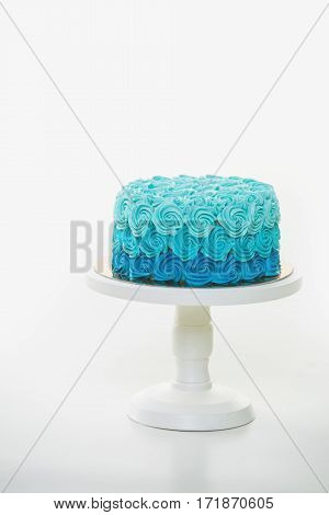 Blue creamy birthday cake on a white cake stand