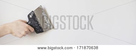 Trowel in man's hand on a background of a white wall. Dirty tools for repair. Tool for getting rid of the wallpaper. Space for text