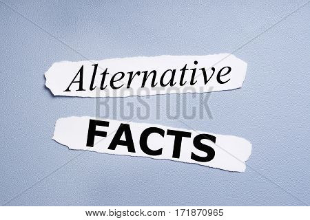 alternative facts, phrase printed on pieces of paper over blue background