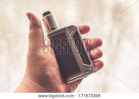 Vaping device in the man's hand. Electronic cigarette or e-cig mod , vape