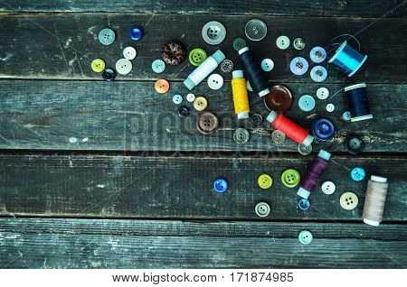 Multicolored buttons and sewing spools on wood grey planks