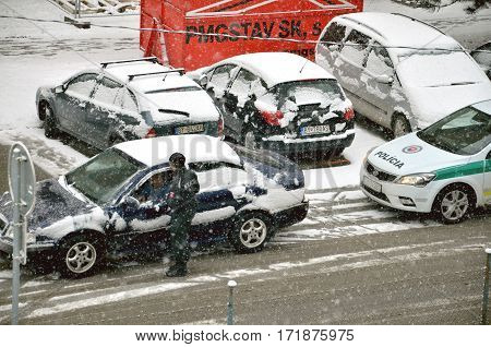 Bytca Slovakia - February 17 2017: Police traffic partol stop a car. Policeman stand outside vehicle in bad weather and talk with driver while snow falls.