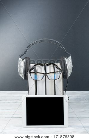 Audiobook on white background. Headphones put over stack of colorful books empty cover copy space for ad text. Distance education e-learning concept. Tablet PC