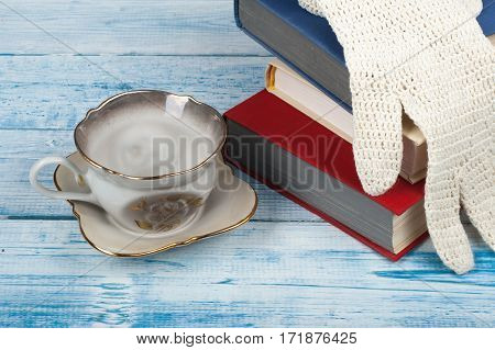 Open book hardback books on wooden table cup and white gloves knitted crochet Back to school. Copy space for text