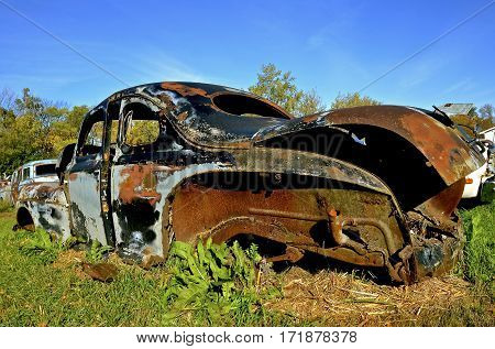 An old car full of patina rusting in a country junkyard