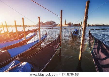 City landscape. Fantastic views of the gondola at sunset, moored on San Marco square with San Giorgio di Maggiore church in the background - Venice, Italy, Europe