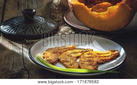 fried in a pan and grill the slices of juicy orange pumpkin with spices country - style in low key