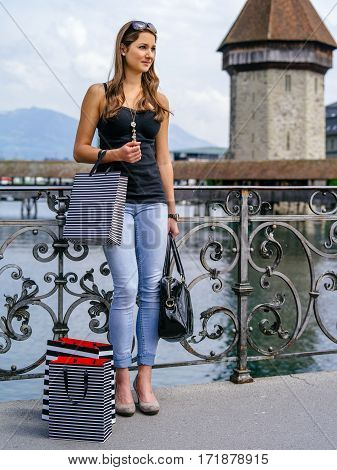 Photo of a beautiful young woman standing with shopping bags in Luzern Switzerland.