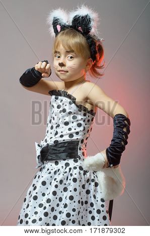 Little Girl Dressed As A Cat On A Gray Background.