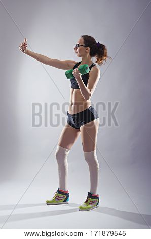 Athletic Woman With A Dumbbell In Your Hand Makes Selfie On A Smartphone.