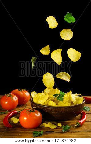 Potato Chips Fall Into A Clay Bowl Isolated On A Black Background.