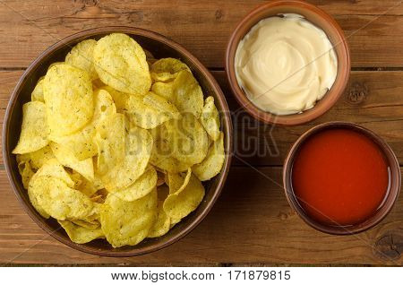Potato Chips And Sauces On A Wooden Table.