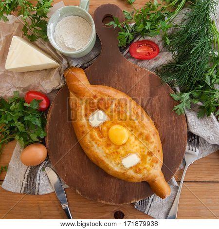 Traditional Georgian adjara khachapuri on the table. Homemade baking. Top view. Flat lay.