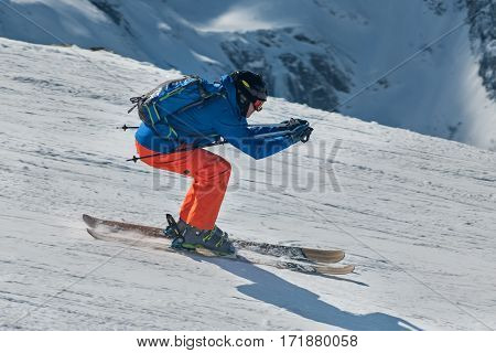 Skier skiing downhill in high winter mountains