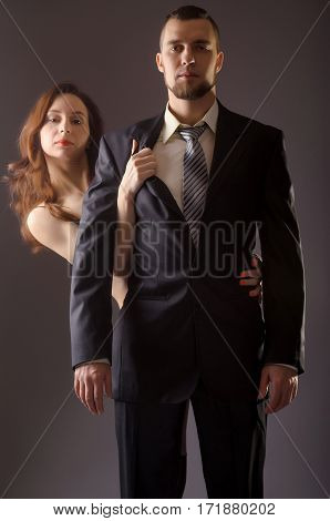 Stylish man in a suit and tie on gray background. Woman hugging a man standing behind him.